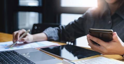 Vrouw met een pen en een telefoon in haar hand berekent financiële zaken achter een latop